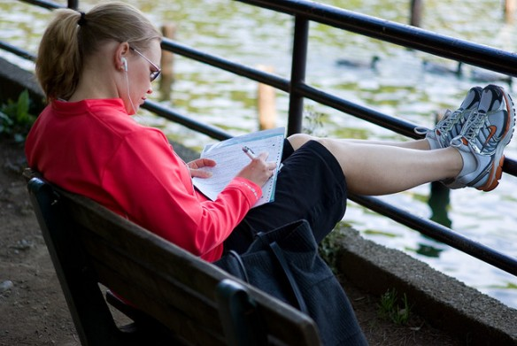woman sitting on park bench writing